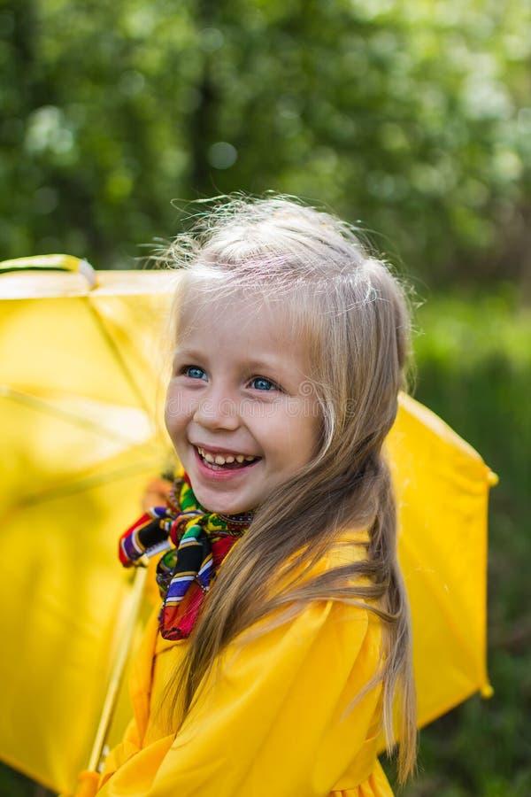 Muchacha sonriente en un vestido amarillo con un paraguas en un día soleado lluvioso de la primavera imagen de archivo libre de regalías