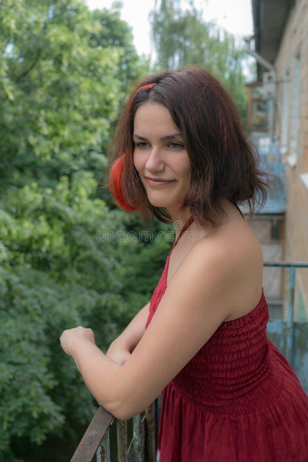 Muchacha sonriente en un vestido rojo imágenes de archivo libres de regalías