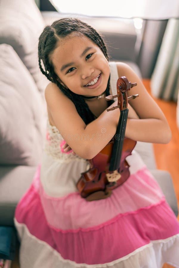 Muchacha sonriente feliz, aprendiendo jugar la música fotos de archivo