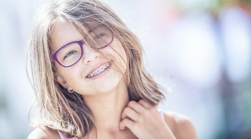 Muchacha sonriente feliz con los apoyos y los vidrios dentales Ca lindo joven imagen de archivo
