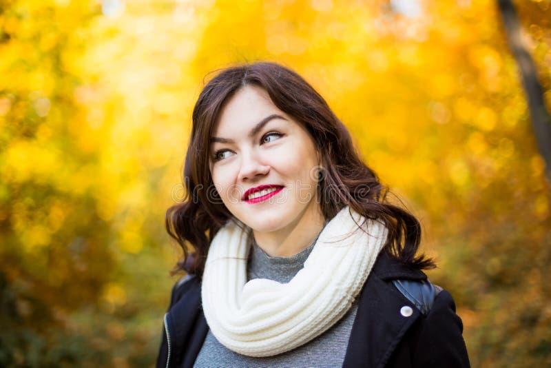 Muchacha sonriente feliz en un fondo del paisaje del otoño imagen de archivo libre de regalías