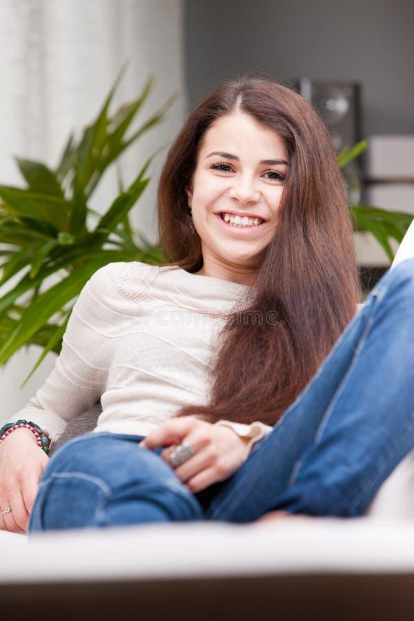 Muchacha sonriente feliz en un sofá imagen de archivo libre de regalías