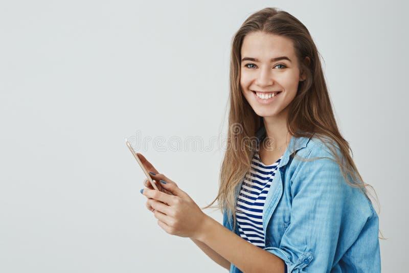 Muchacha sonriente feliz encantadora que sostiene la tableta digital que goza usando la cámara de torneado del artilugio a estre imagen de archivo libre de regalías