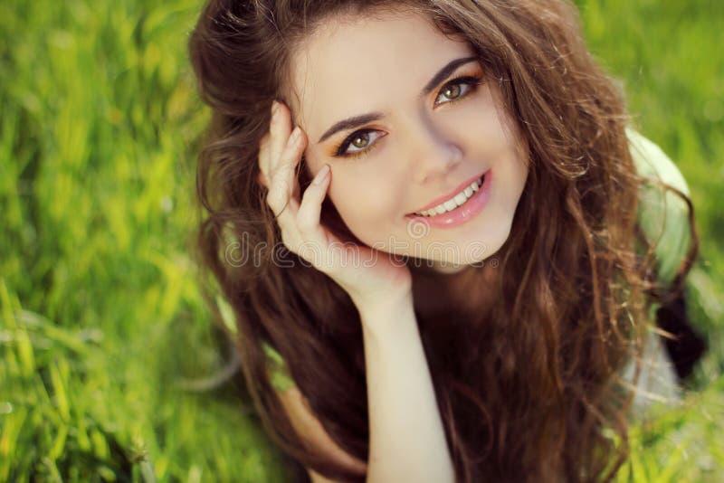 Muchacha sonriente feliz que descansa sobre la hierba verde, al aire libre retrato foto de archivo