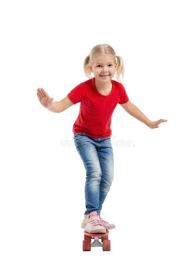 Muchacha sonriente feliz que monta un monopatín foto de archivo libre de regalías