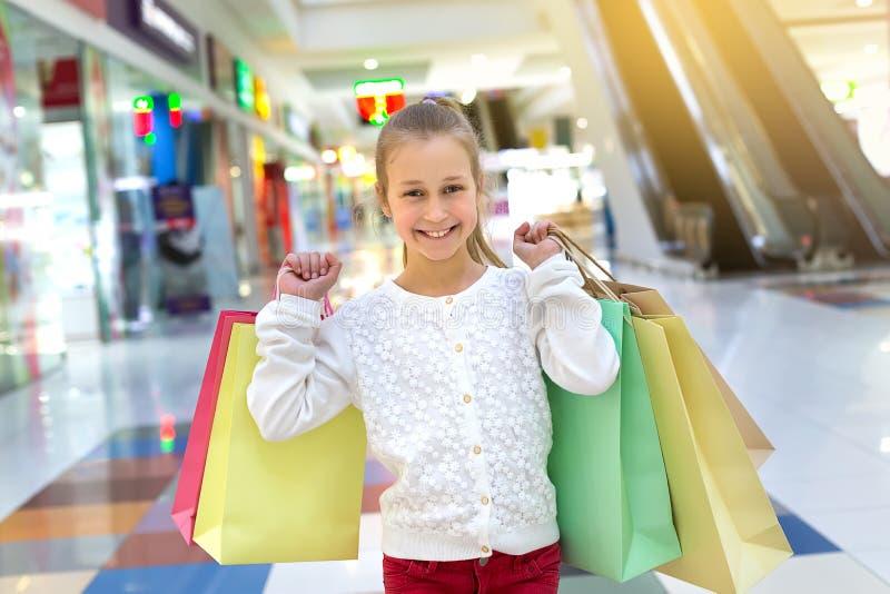 Muchacha sonriente feliz que sostiene bolsos de compras en centro comercial foto de archivo libre de regalías