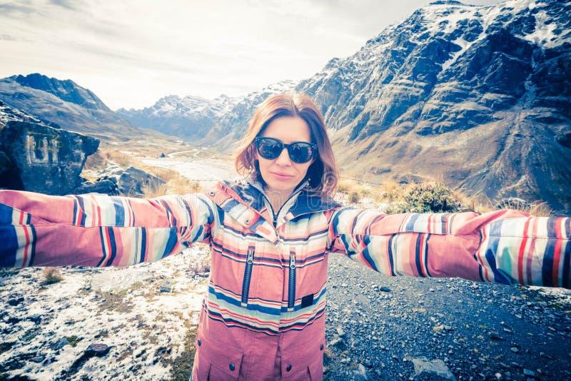 Muchacha sonriente feliz que toma el selfie en los Andes rocosos imagen de archivo