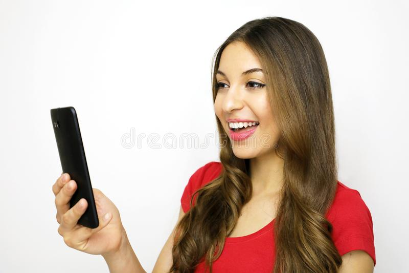 Muchacha sonriente feliz que usa el teléfono elegante en el fondo blanco imagenes de archivo