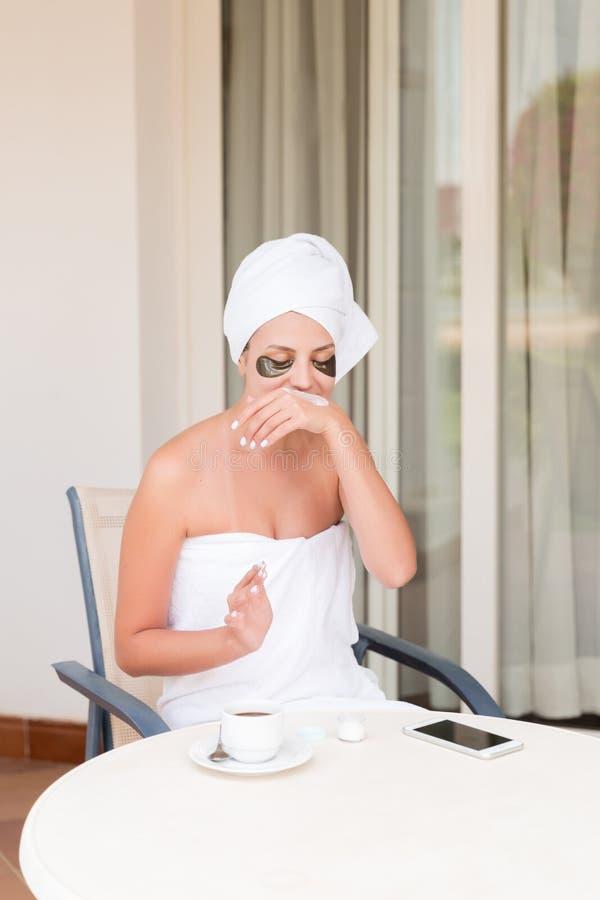 Muchacha sonriente feliz temprano por la mañana en la terraza del hotel para manchar sus manos con una crema de piel hidratante b imágenes de archivo libres de regalías