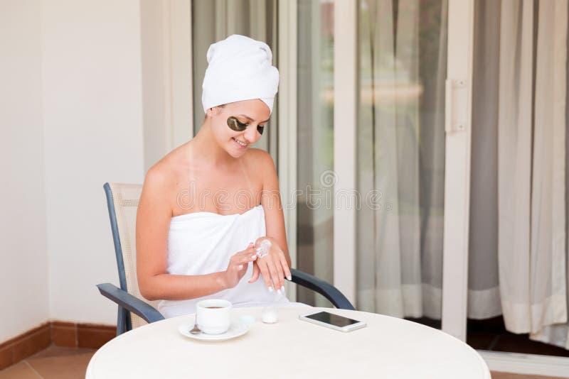 Muchacha sonriente feliz temprano por la ma?ana en la terraza del hotel para manchar sus manos con una crema de piel hidratante b imagen de archivo