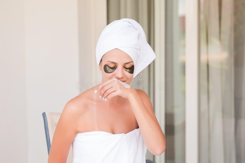 Muchacha sonriente feliz temprano por la ma?ana en la terraza del hotel para manchar sus manos con una crema de piel hidratante b fotos de archivo libres de regalías