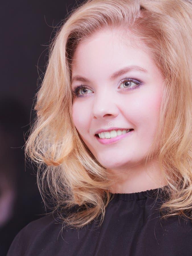 Muchacha sonriente hermosa con el pelo ondulado rubio en salón de belleza de la peluquería imagen de archivo libre de regalías
