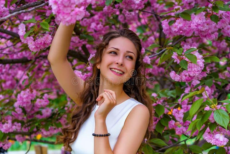 Muchacha sonriente hermosa con el pelo rizado en el vestido blanco en el jardín en flores rosadas del flor imagenes de archivo
