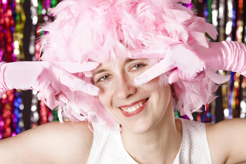 Muchacha sonriente hermosa con la peluca del plumaje rosado imagen de archivo