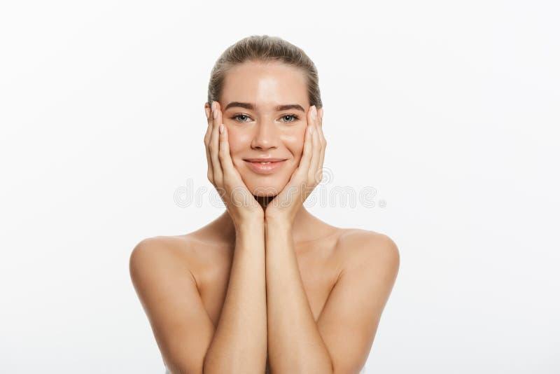 Muchacha sonriente hermosa con la piel limpia, el maquillaje natural, y los dientes blancos en fondo gris fotos de archivo