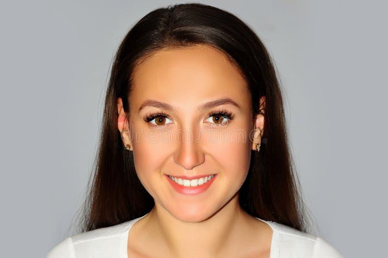Muchacha sonriente hermosa con la piel limpia, el maquillaje natural, y el whi imágenes de archivo libres de regalías