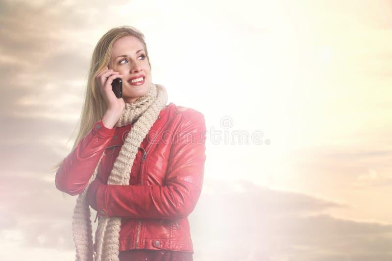 Muchacha sonriente hermosa en el teléfono fotos de archivo