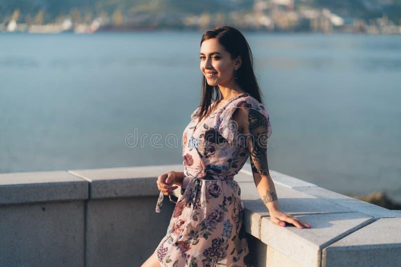 Muchacha sonriente hermosa en el vestido del verano que presenta en tiempo de la puesta del sol en la costa fotografía de archivo libre de regalías