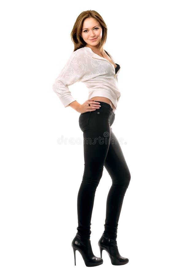 Muchacha sonriente hermosa en pantalones vaqueros apretados negros foto de archivo