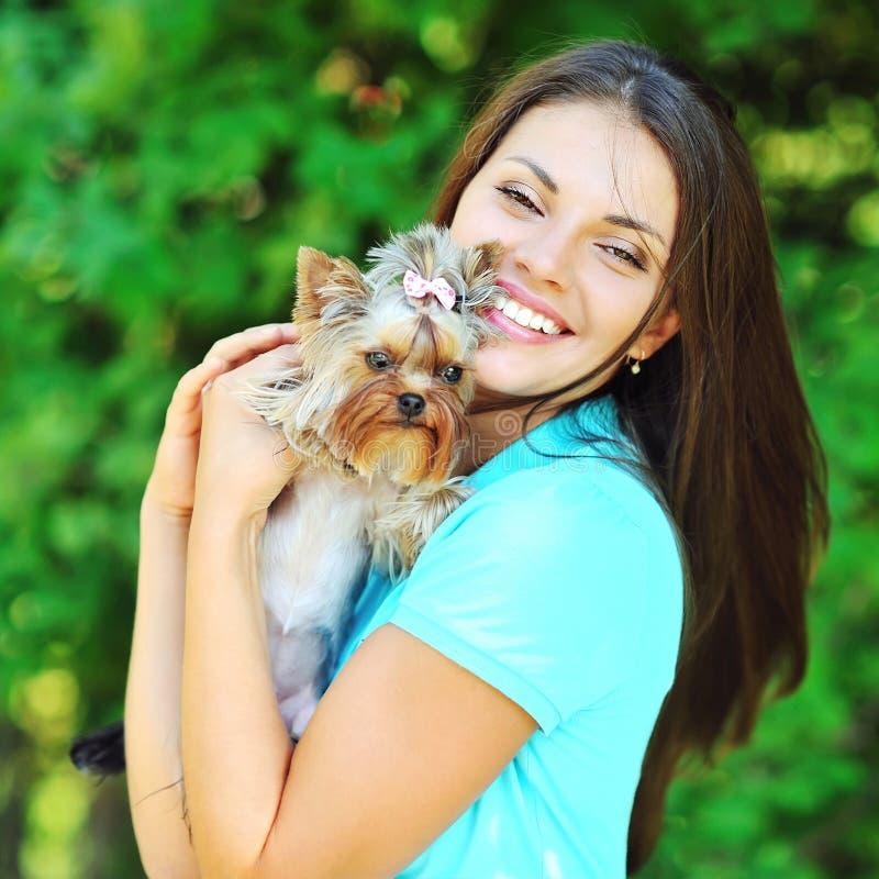 Muchacha sonriente hermosa que abraza su terrier de Yorkshire del perrito imagenes de archivo