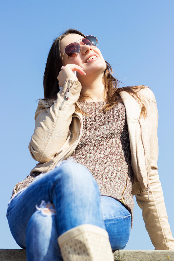 Muchacha sonriente hermosa que habla en el teléfono móvil imagen de archivo libre de regalías