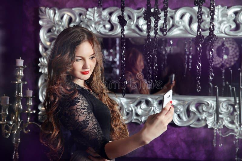 Muchacha sonriente hermosa que hace el selfie en interior moderno de lujo imagen de archivo