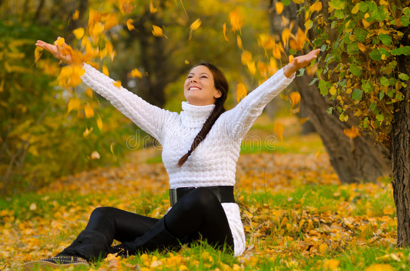 Muchacha sonriente hermosa que lanza las hojas secas en el aire foto de archivo libre de regalías