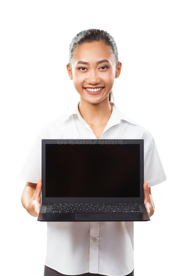 Muchacha sonriente joven asiática linda que sostiene y que muestra el ordenador portátil aislado foto de archivo