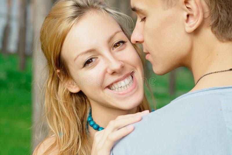 Muchacha sonriente joven besada por un muchacho fotos de archivo libres de regalías