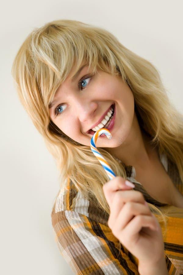 Muchacha sonriente joven con el caramelo de azúcar imágenes de archivo libres de regalías