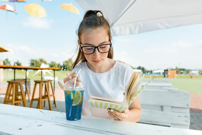 Muchacha sonriente joven del adolescente que descansa en café al aire libre del verano, libro de lectura de la muchacha y ensalad imagen de archivo libre de regalías
