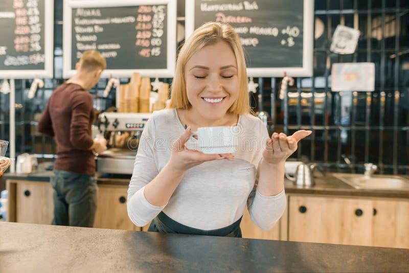 Muchacha sonriente joven del barista con la taza de café Mujer rubia en delantal que disfruta del aroma del café fresco, cerca de fotos de archivo libres de regalías