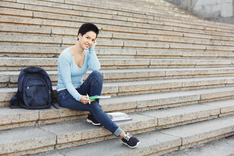 Muchacha sonriente joven del estudiante que hace notas en cuaderno fotografía de archivo