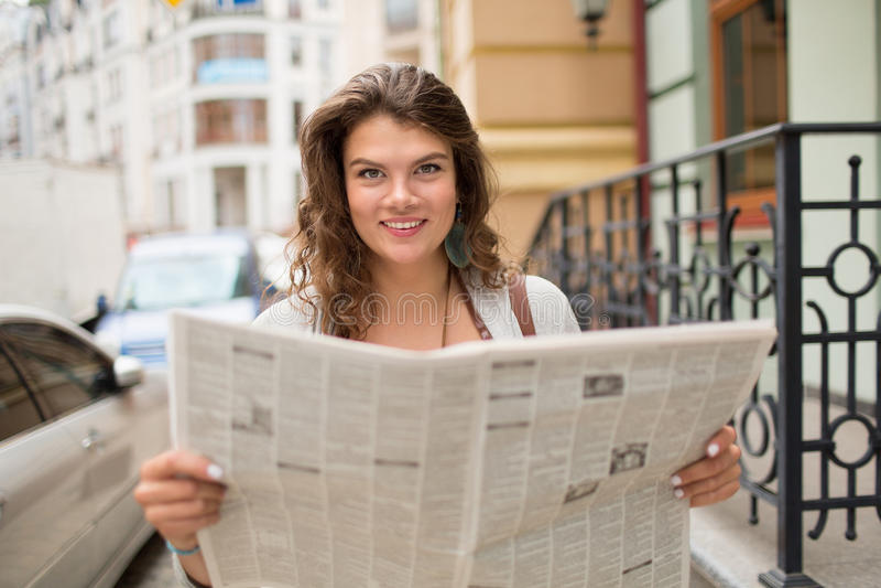 Muchacha sonriente joven del tavel que sostiene el periódico fotos de archivo