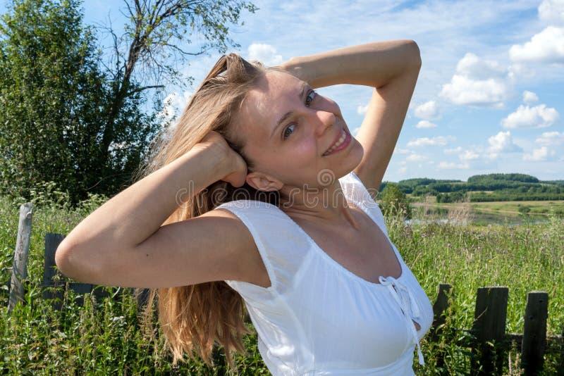 Muchacha sonriente joven en el vestido blanco con los brazos aumentados en el fondo del paisaje del verano imágenes de archivo libres de regalías