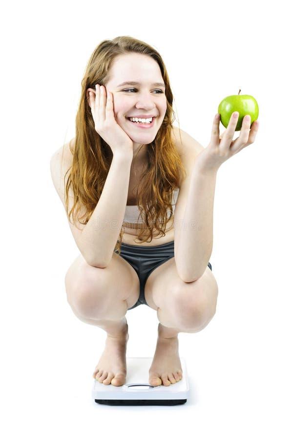 Muchacha sonriente joven en manzana de la explotación agrícola de la báscula de baño fotos de archivo libres de regalías