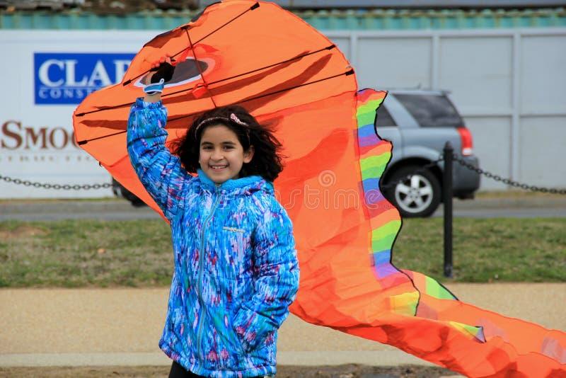 Muchacha sonriente joven que consigue lista para volar su cometa en el festival de la cometa, Washington DC, abril de 2015 fotos de archivo
