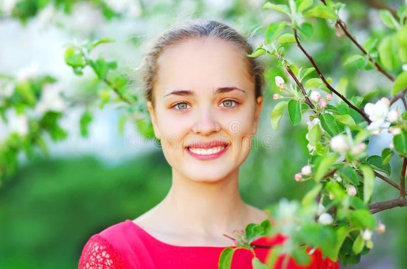 Muchacha sonriente linda del retrato en jardín de la primavera foto de archivo