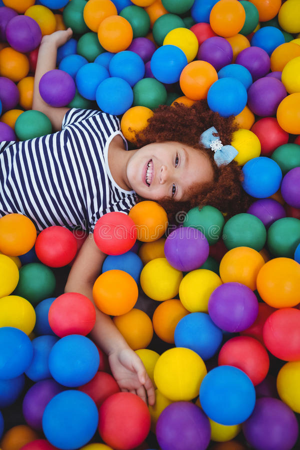 Muchacha sonriente linda en piscina de la bola de la esponja fotografía de archivo libre de regalías