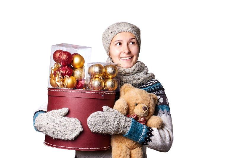 Muchacha sonriente linda joven en el suéter, sosteniendo una caja de decoraciones de la Navidad Invierno, Cristmastime, día de fi imágenes de archivo libres de regalías
