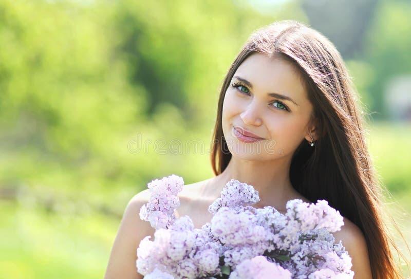 Muchacha sonriente linda preciosa con un ramo de lilas imagen de archivo libre de regalías