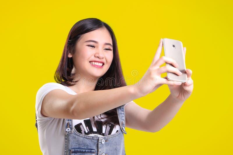 Muchacha sonriente linda que toma el selfie, sobre amarillo foto de archivo