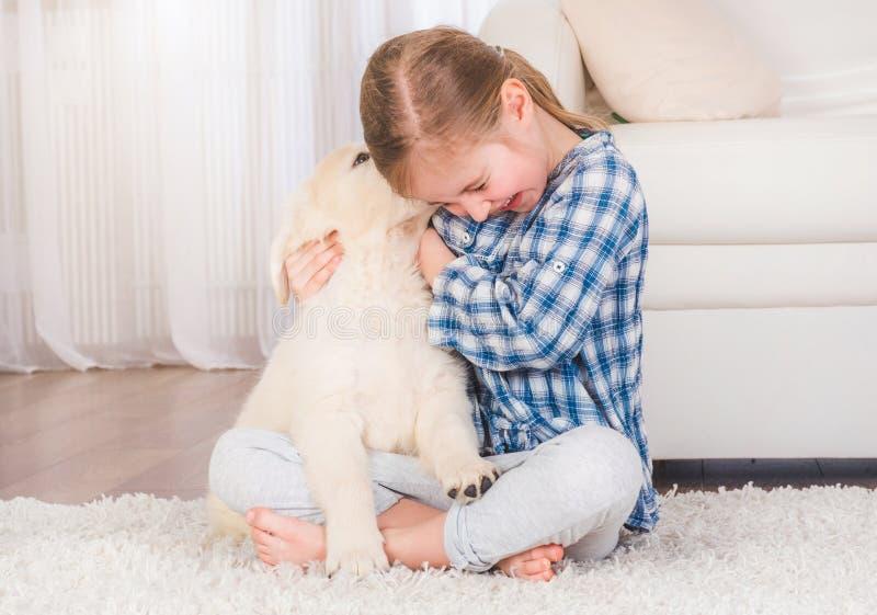 Muchacha sonriente que abraza el perrito del perro perdiguero imagen de archivo libre de regalías