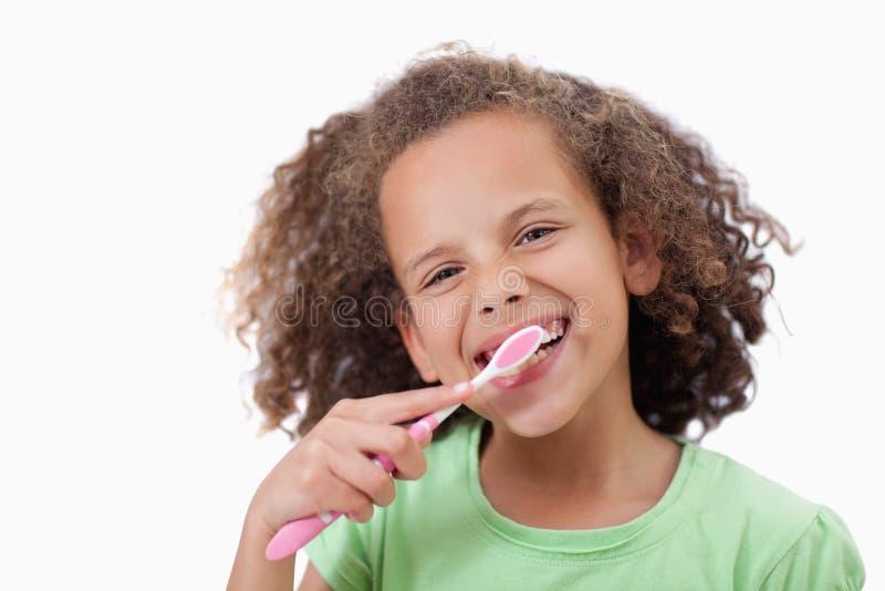 Muchacha sonriente que cepilla sus dientes fotografía de archivo libre de regalías