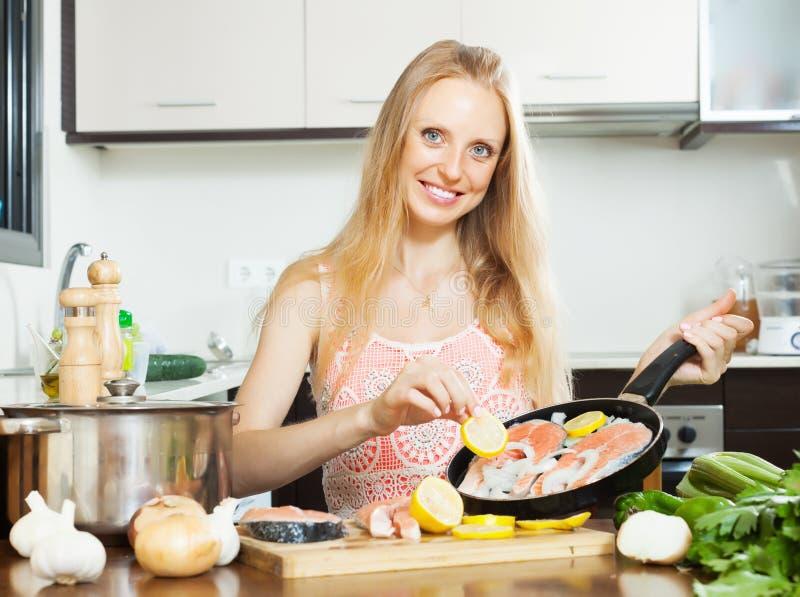 Muchacha sonriente que cocina los pescados de color salmón con el limón foto de archivo