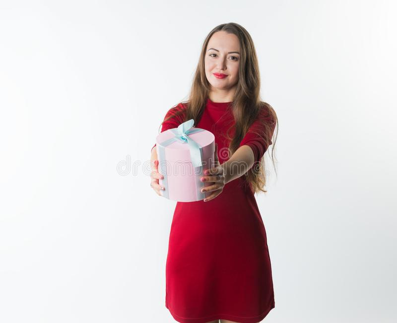 Muchacha sonriente que da la caja con los regalos a la cámara fotografía de archivo