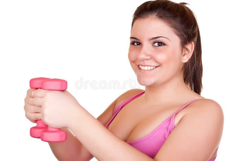 Muchacha sonriente que ejercita con los pesos fotografía de archivo