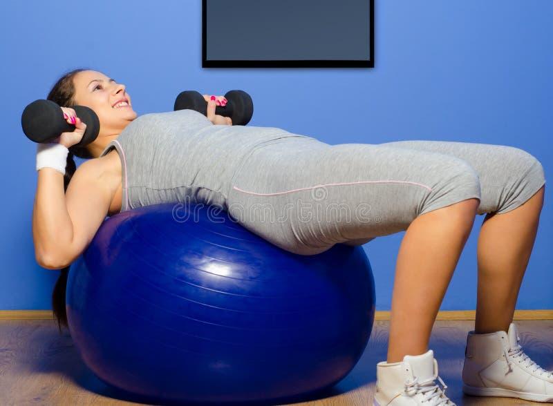 Muchacha sonriente que ejercita con pesas de gimnasia foto de archivo