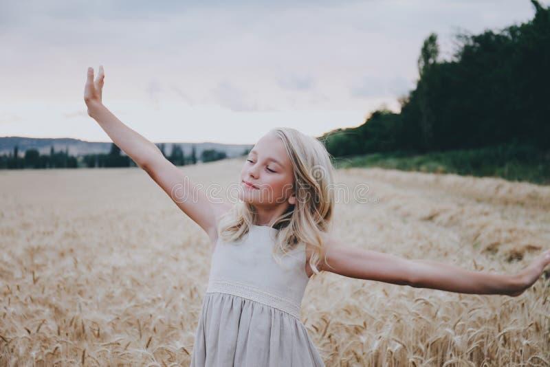 Muchacha sonriente que estira en un campo de trigo imagen de archivo libre de regalías
