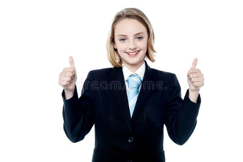Muchacha sonriente que gesticula los pulgares dobles para arriba imagenes de archivo